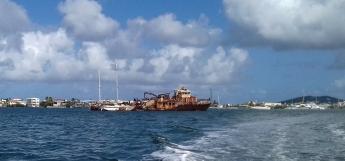 Au milieu de la lagune, des épaves de gros bateaux servent de ponton d'amarrage à des voiliers en piteux état